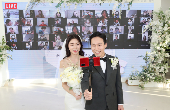 """Park Ji-ye and Ha Ji-soo became the first couple in the country to be wedded online, with the help of telecommunication company KT as part of their campaign """"Caring About You."""" [KT]"""