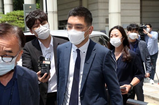 Channel A Reporter Lee Dong-jae, center, exits a courthouse after attending a hearing on a warrant for his arrest over allegations that he colluded with a high-ranking prosecutor to implicate a ruling party-affiliated media personality. [YONHAP]