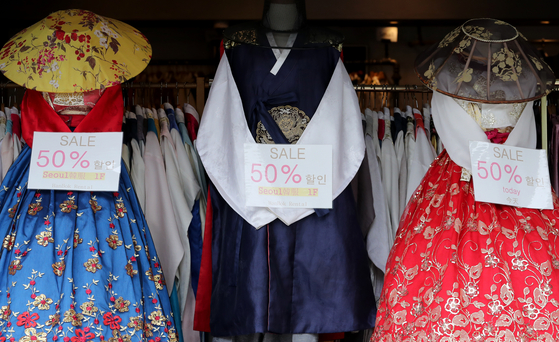 Hanbok (traditional Korean clothing) are half off at a store in central Seoul Monday. Many hanbok rental stores were shut down, with the absence of tourists and as entry to royal palaces has been suspended due to the coronavirus pandemic. Palaces are set to reopen Wednesday, the Cultural Heritage Administration announced Monday. [CHOI JEONG-DONG]