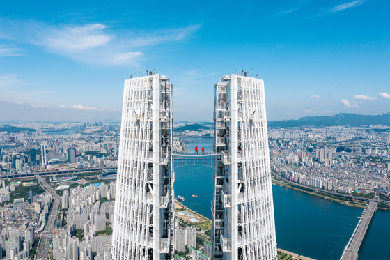"""Seoul Sky, the observatory at the top of the Lotte World Tower in Songpa District, southern Seoul, said last week it is launching the 'Sky Bridge Tour"""" program this Friday. The new tour is a high-altitude experience at 541 meters (1,775 feet) above ground, where visitors get to walk across the bridge that connects the two separate structures at the very top of the tower. [YONHAP]"""