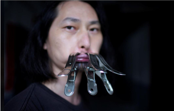 Chinese performance artist Brother Nut clamps his mouth shut on July 13 as part of a protest against censorship following the outbreak of coronavirus. [REUTERS/YONHAP]