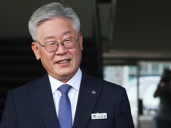 Gyeonggi Governor Lee Jae-myung smiles on Thursday at a press conference outside the Gyeonggi Provincial Government office building, after the Supreme Court acquitted him of an election law violation charge.  [YONHAP]