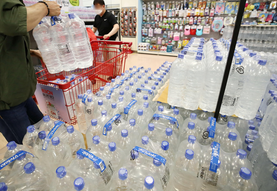 A customer loads bottled water at a discount store in Seoul, Monday. After larva-like organisms were spotted in tap water in Incheon earlier this month, sales of bottled water close to doubled over the past four days compared with the same period last week, at convenience stores near the area. Water filters for faucets and shower heads were also popular online. [YONHAP]