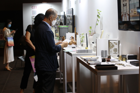 An interior design company executive looks at products displayed at the Contemporary European Design exhibition held at Hotel Shilla in central Seoul on Tuesday. Due to the coronavirus pandemic, many Korean and European Union companies participated in the exhibition online. [YONHAP]