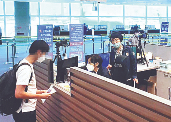 Kim Jin-sook, a senior health official at the Incheon Airport National Quarantine Station, right, helps check a passenger's temperature. [Incheon Airport National Quarantine Station]