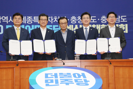 Local government heads of Sejong and Chungcheong provinces and Democratic Party (DP) Chairman Lee Hae-chan, center, sign a statement supporting a plan to relocate the National Assembly and Blue House to Sejong city on Tuesday.  [YONHAP]