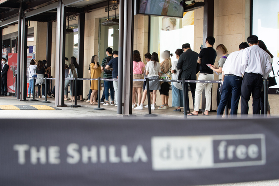 A long line forms in front of The Shilla Duty Free next to Hotel Shilla on Tuesday. As overseas travel has been limited, duty-free businesses have been selling to domestic customers. [YONHAP]