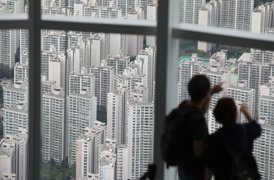 Visitors look at the apartment complex of Songpa District, Southern Seoul. [YONHAP]