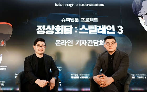 "Kakao Page CEO Lee Jin-soo, left, and director Yang Woo-seok at an online press event to discuss their crossover project on the ""Steel Rain"" series. [KAKAO PAGE]"