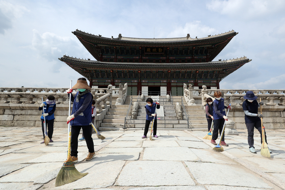 Workers from the Cultural Heritage Administration clean the courtyard of Gyeongbok Palace in central Seoul on Tuesday, as ancient palaces are set to reopen Wednesday, 55 days after closing amid a surge in Covid-19 cases. [NEWS1]