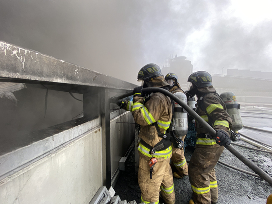 Firefighters work to put out a fire at the SLC Distribution Center in Yongin, Gyeonggi on Tuesday. Most of the 69 workers at the center when the fire started, around 8:30 a.m., were in the fourth basement level. Five were found dead and 64 were rescued. Eight of those rescued sustained serious injuries, and one was in critical condition. According to witnesses, a fire started after an explosion in a freight truck, which was loading frozen processed foods. The sudden explosion and ensuing smoke appeared to have impeded workers as they attempted to escape, the National Fire Agency said. [YONHAP]