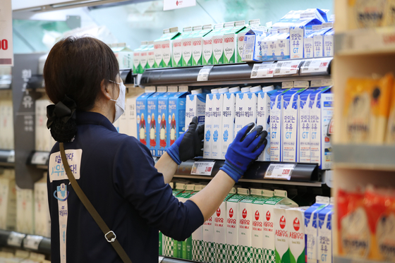 An employee organizes cartons of milk on the shelves of a discount store in Seoul Wednesday after the dairy industry decided to freeze raw milk prices, which determine the price of dairy products, to ease the economic impact from the coronavirus pandemic. Prices of a liter of raw milk, which is determined every two years, will stay the same until next August when a 21 won increase per liter kicks in. [YONHAP]