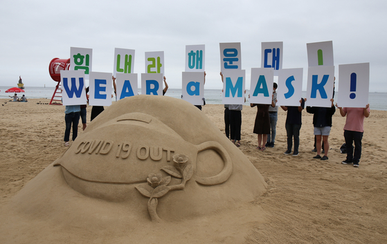 """Campaigners hold cards reading """"Wear a mask"""" on Haeundae Beach, one of the most visited beaches in Busan, on July 22, behind a sand sculpture with the same message. From July 25, visitors to five main beaches in Busan including Haeundae are required to wear a mask and will be fined a maximum of 3 million won ($2,500) if spotted without one. [YONHAP]"""