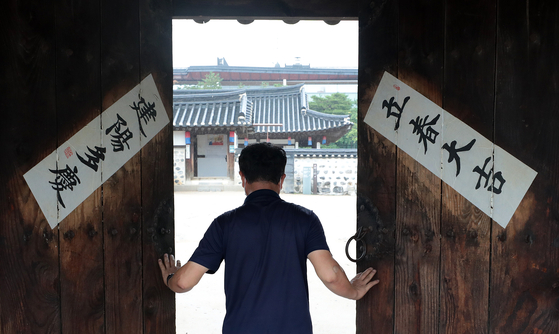 The door to a traditional Korean hanok house is opened Wednesday as the Namsangol Hanok Village in Jung District, central Seoul, welcomed visitors for the first time in weeks due to a surge in Covid-19 cases. Some 65 other cultural facilities in Seoul reopened the same day. [NEWS1]