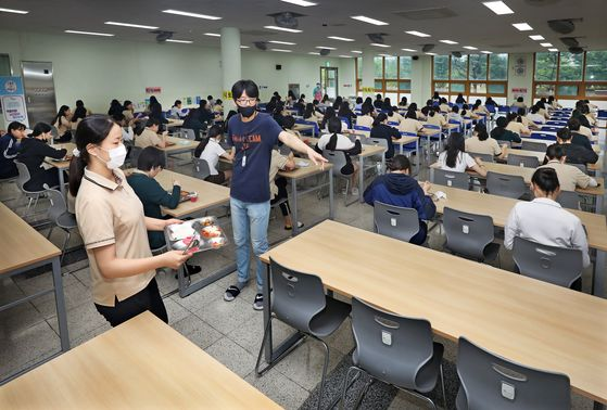 A teacher guides a student to her seat in the school's cafeteria, where social distancing is practiced. [PARK SANG-MOON]