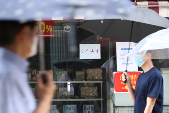 A store in Myeong-dong, central Seoul, is closed temporarily on Thursday due to the recent increase in Covid-19 infections. Amid the coronavirus pandemic, the GDP of the country declined 3.3 percent in the second quarter, following a 1.3 percent decline in the previous quarter, according to the Bank of Korea. [YONHAP]