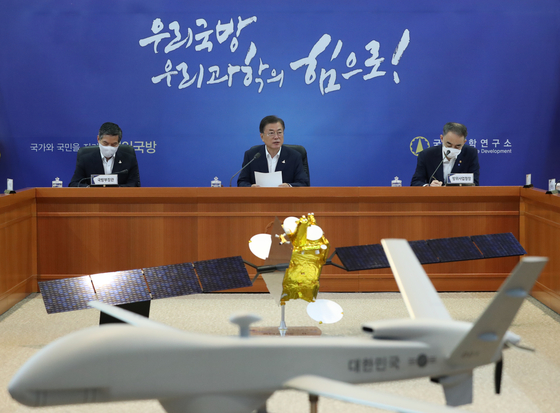President Moon Jae-in, center, delivers an address to the Agency for Defense Development during a rare visit to the institute on Thursday. In the foreground is a model of Korea's first domestically produced mid-altitude aerial surveillance drone, currently under development by the agency. [YONHAP]