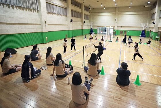 Students in face masks play badminton during a physical education class. [PARK SANG-MOON]