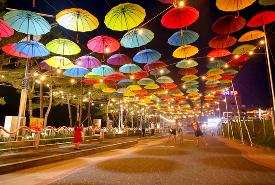 Visitors take photos at a road decorated with umbrellas next to Mallipo Beach in Taean County, South Chungcheong, on Wednesday night, after the road was designated as a pedestrian zone until July 30. [YONHAP]