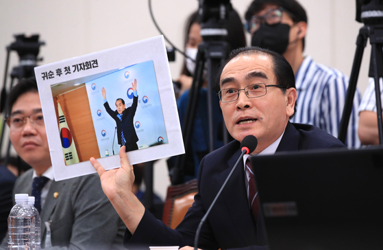 Rep. Thae Yong-ho, a former North Korean diplomat and current lawmaker of the conservative United Future Party, at Lee's confirmation hearing shows off a photograph of himself at a press conference following his defection to the South, arguing it proves he has renounced North Korea's Communist ideology in contrast to Unification Minister nominee Lee In-young. [YONHAP]