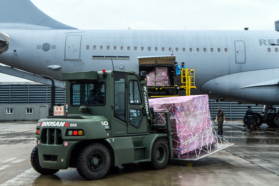 Soldiers load a military plane with face masks and other protective gear Thursday at an Air Force base in Gimhae, South Gyeongsang. Two KC-330 air refueling tankers departed that day for Iraq on a mission to bring home some 300 Korean construction workers. [YONHAP]