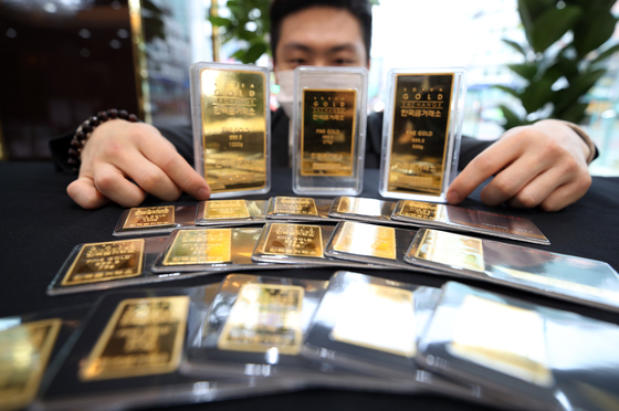 A man displays gold bars at the Korea Gold Exchange office in Jongno District, central Seoul, on Thursday. The price of gold bars on Thursday surged to an all-time high of 72,451 won ($60) per gram since the establishment of the gold trading market in Korea in 2014. [YONHAP]