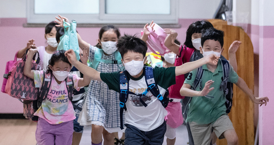 Children who just ended their last day of classes run out of the school in Gangseo District, western Seoul, on Thursday. [NEWS1]