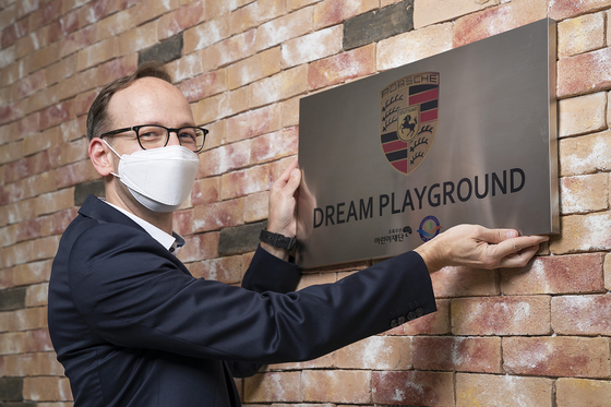 Holger Gerrmann, CEO of Porsche Korea, delivers a nameplate for Porsche Dream Playground in Saesol School in Gimpo on July 22.