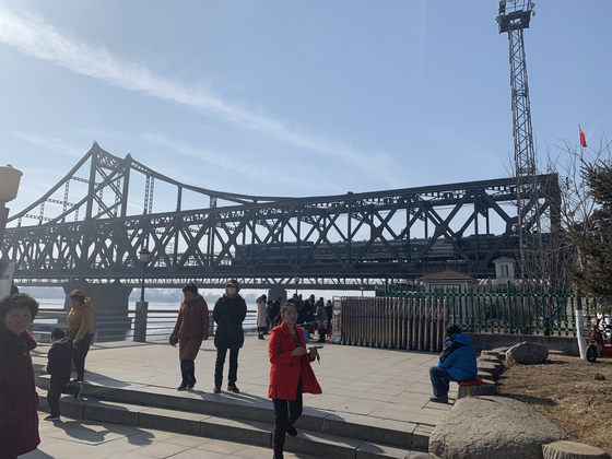Visitors walk under the Yalu River Bridge, which connects Sinuiju, North Korea and Dandong, China. China occupies the highest percentage of North's international trade volume. [YONHAP]