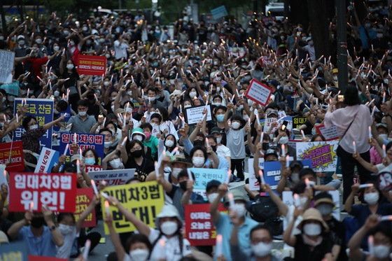 Thousands of people stage a candlelight vigil to protest the government's retroactive application of higher property and capital gains taxes in front of the Korea Deposit Insurance Corporation in downtown Seoul on Saturday evening. [YONHAP]