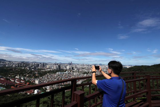 A man appreciates the clean, blue sky from an observatory on Mount Namsan in Seoul on Sunday after heavy rainfall earlier in the weekend. Another rainy front will move northward on Monday afternoon, the weather agency forecast. [KIM SANG-SEON]