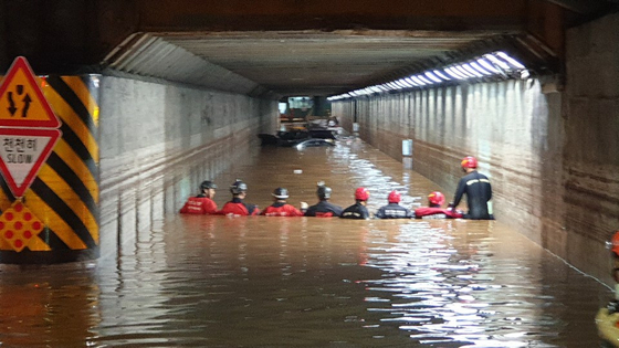 Fire fighters rescue trapped passengers after the flooding of an underpass in Busan's Dong District Thursday due to torrential rainfall which killed three people. [BUSAN METROPOLITAN POLICE AGENCY]