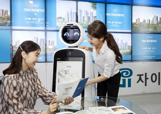 Models check out GS Engineering & Construction's artificial intelligence (AI) guide called Xibot. According to GS E&C on Monday, the AI robot will be used at its model houses for new apartment complexes, a first for the industry. [YONHAP]