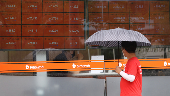 A passerby looks at the prices of cryptocurrencies taped onto the windows of the cryptocurrency exchange Bithumb on Monday in Gangnam District, southern Seoul. Bitcoin, a type of cryptocurrency, was trading above $10,000 or 12 million won for the first time since early June at 7 a.m. Monday, due to growing demand as the economy worsens across the globe. The virtual currency also went through its third so-called halving on May 11, which cut the rewards given to those who mine bitcoin. [YONHAP]