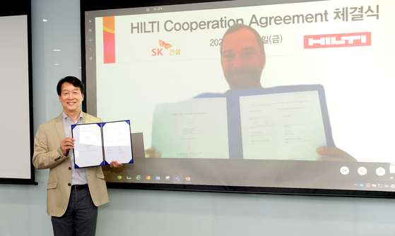 Yoon Hyuk-noh, managing director of the Hi-Tech Division at SK E&C, left, and Reinhard Schindler, Executive Vice President of Hilti Corporation, celebrate the agreement signed by the two parties on Friday. [SK E&C]