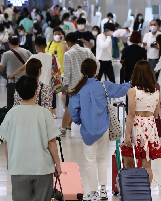 Tourists check in early on Monday morning at the domestic terminal at Gimpo International Airport in Gangseo District, western Seoul, before they take off on their summer vacations. [YONHAP]