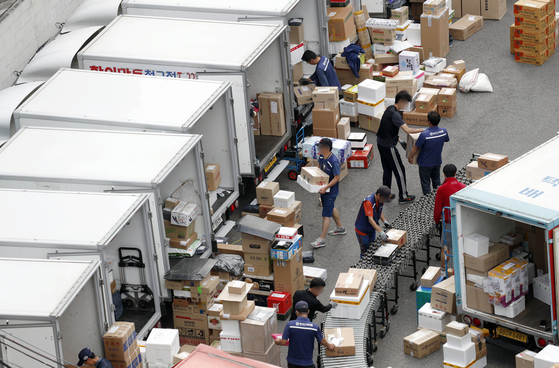 Delivery workers sort parcels at a delivery center in Seoul. [NEWS1]