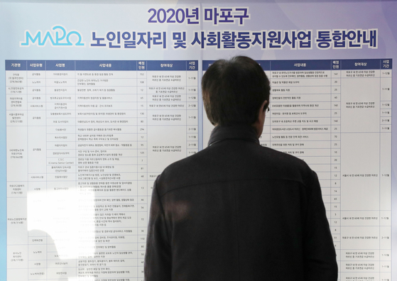 An elderly job applicant looks at job postings at the Mapo District Office in December last year. [YONHAP]