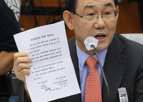Rep. Joo Ho-young of the United Future Party shows a copy of what he called a secret deal signed by Park Jie-won in 2000, during Park's confirmation hearing on Monday to become the National Intelligence Service head. The document includes a promise to pay North Korea to arrange the historic inter-Korean summit.  [YONHAP}