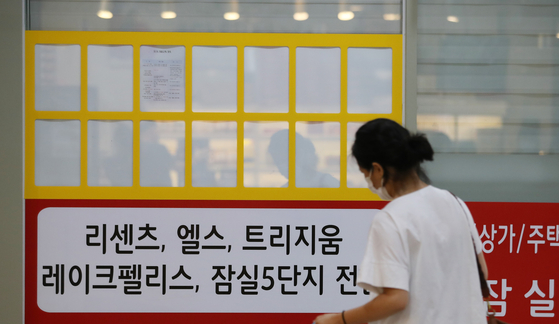 A person looks at a bulletin on the empty window of a real estate agent's office Wednesday, in Songpa District, southern Seoul. As a standing committee passed the tenant protection law Wednesday, which protects jeonse tenants up to 4 years and limits price increases, the real estate market is seeing a massive shortage in supply of such properties, pushing the price up for 52 consecutive weeks. The ruling Democratic Party urged for the bill to be put to a vote as soon as possible. [YONHAP]