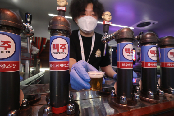 A craft beer company employee offers a sample during the Korea International Beer Expo held at the aT Center in Yangje, southern Seoul on Thursday. The expo, celebrating its second year and open until Saturday, has 123 beer companies participating including those from the United States and Germany. This year the expo is holding a tasting competition sponsored by Germany's Rastal. [YONHAP]