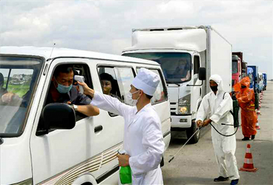 """North Korea's state-run Rodong Sinmun publishes Friday a photo of public health authorities measuring a driver's temperature as a preventive measure for the coronavirus pandemic. The North has called for 'maximum alert"""" against the pandemic earlier this month. [YONHAP]"""