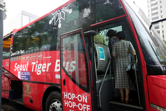 Passengers get on the Seoul City Tour Bus on Aug. 2 near Gwanghwamun Station in central Seoul, a day after the bus service resumed operations. [YONHAP]