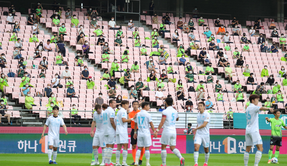 Football fans sit in the stands, socially distanced, to watch a football game between Jeonbuk Hyundai Motors and Pohang Steelers at Jeonju World Cup Stadium on Saturday. The Korean government on July 24 announced that fans will be allowed to watch professional games in stadiums, with seats limited to 10 percent of capacity. [NEWS1]