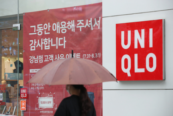 """A sign at the Gangnam branch of Japanese apparel store Uniqlo in central Seoul on Aug. 2 reads the store will suspend its operations. Uniqlo recently announced it will shutter nine branches of its operations in Korea within this month, citing """"changing consumption trends in the retail industry, the spread of Covid-19 and the deteriorating relationship between Korea and Japan."""" [YONHAP]"""