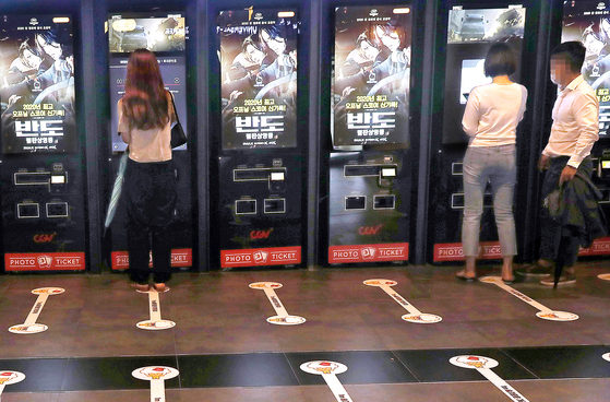 Visitors buy tickets at automated ticket booths in a cinema in Seoul on July 19. [YONHAP]