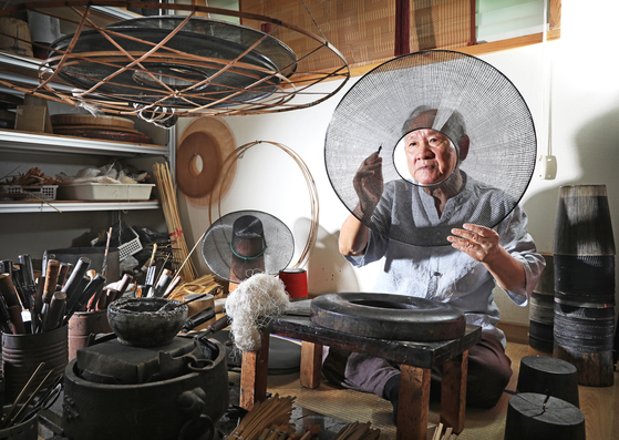 Master craftsman Park Chang-young, who was designated as No.4 intangible cultural property in 2000 for his expertise at making gat, is working on the traditional Korean hat at his studio located in Gwangmyeong, Gyeonggi. [PARK SANG-MOON]