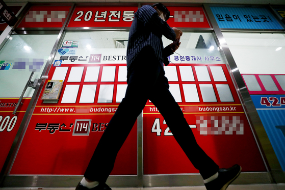 A person walks by an empty bulletin of a real estate agent's office in Songpa District, southern Seoul. [YONHAP]