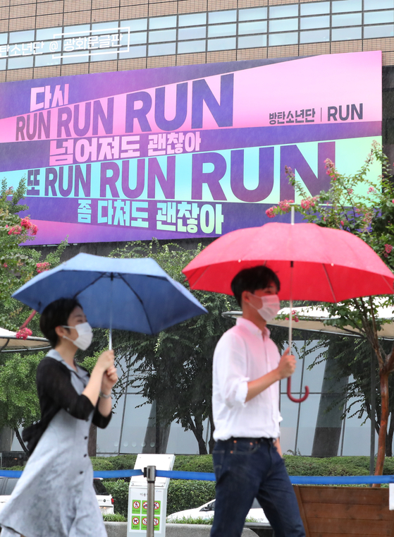 "Pedestrians walk past a billboard covered in lyrics from K-pop boy band BTS on Monday, in Gwanghwamun, central Seoul. Kyobo Life Insurance which owns and manages the billboard said it decorated it with lyrics from BTS's song ""Run"" (2015) to cheer up people exhausted from the prolonged pandemic. [NEWS1]"