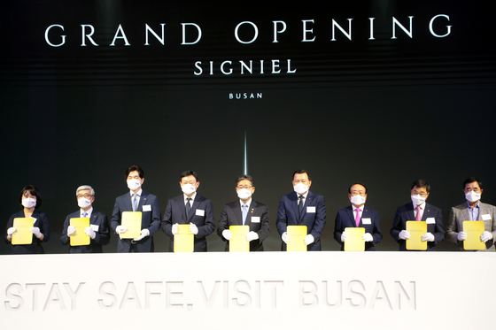 Executives from Lotte are on stage to celebrate the opening of Signiel Hotel Busan in June. [SONG BONG-GEUN]